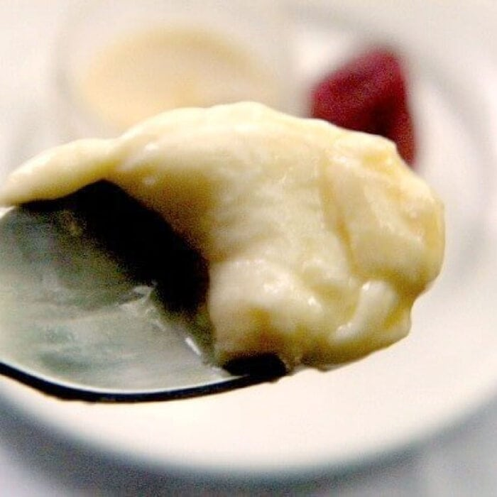 A spoonful of creme caramel being raised from the dish.