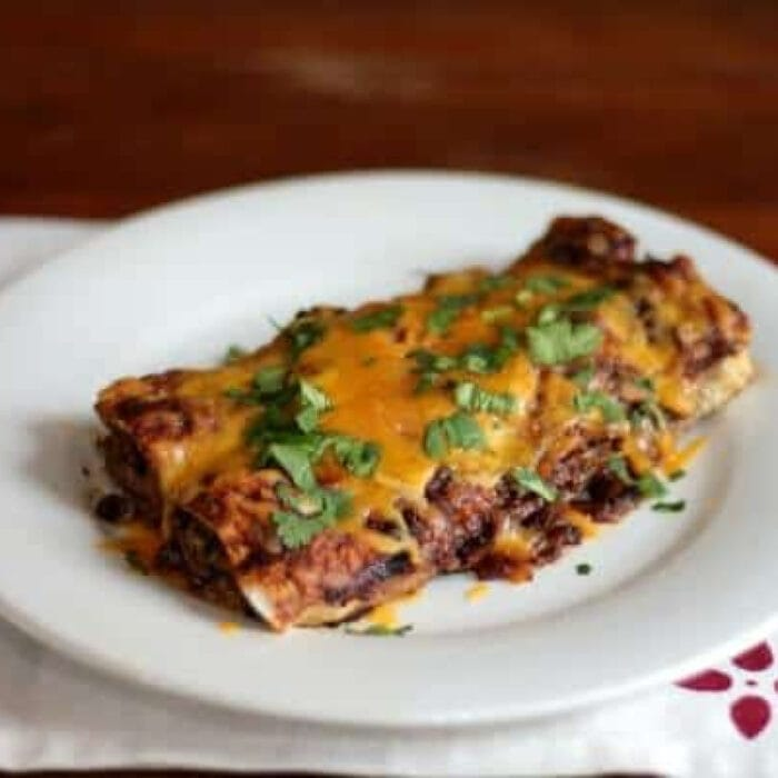 Beef enchiladas on a white plate.