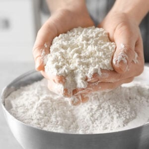 A woman's hands holding white flour above a bowl.