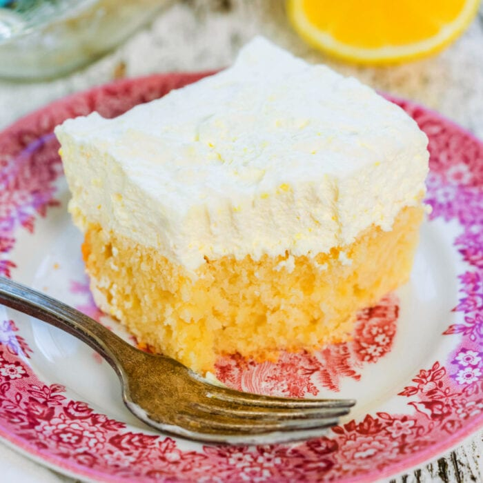 Square of lemon cream cake on a red and white plate.