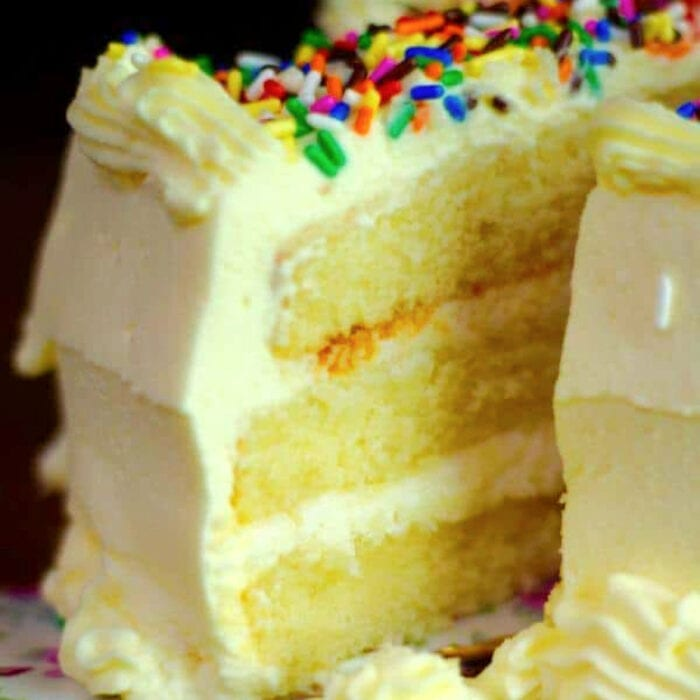 A triple layer lemon cake with whipped lemon buttercream frosting with a slice being removed.