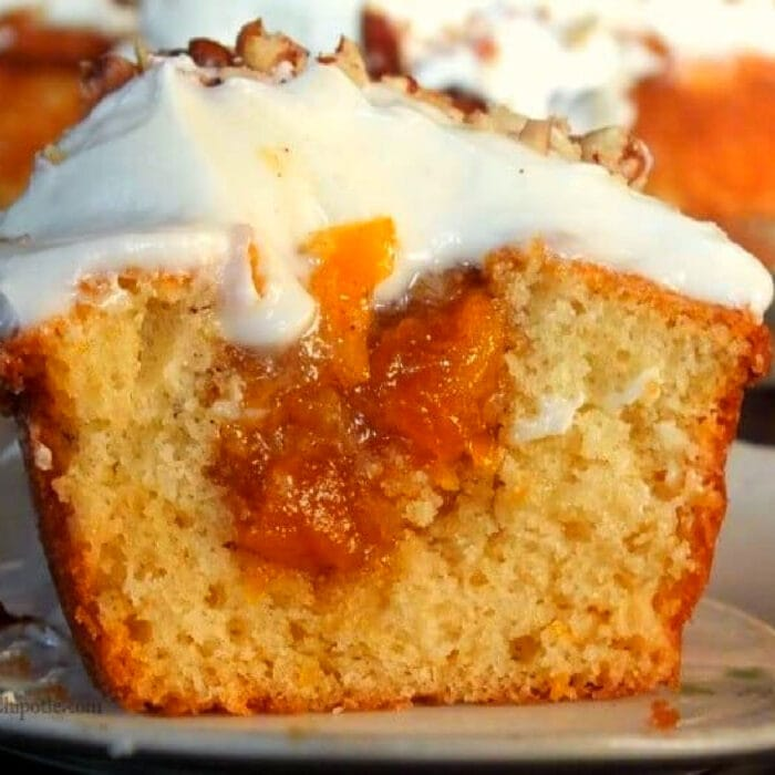 A peach cupcake sliced in half to show the filling.