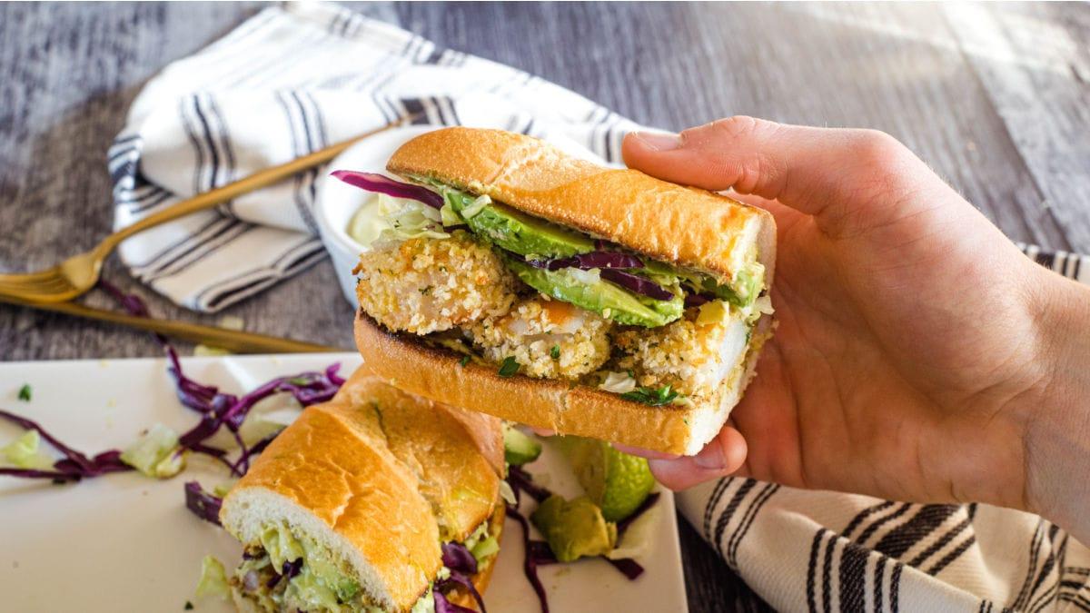 A hand holding half of a po' boy sandwich.