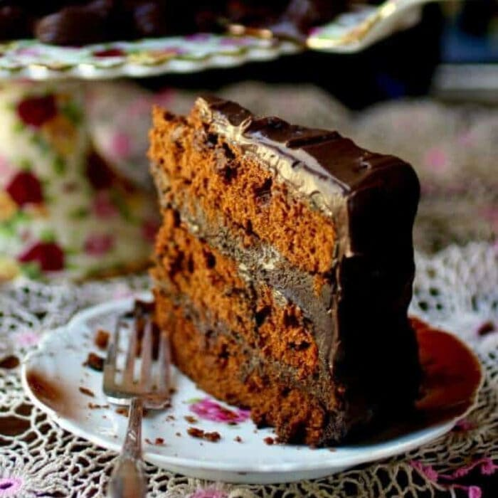 A slice of a triple layer spiced devil's food cake with chocolate frosting.
