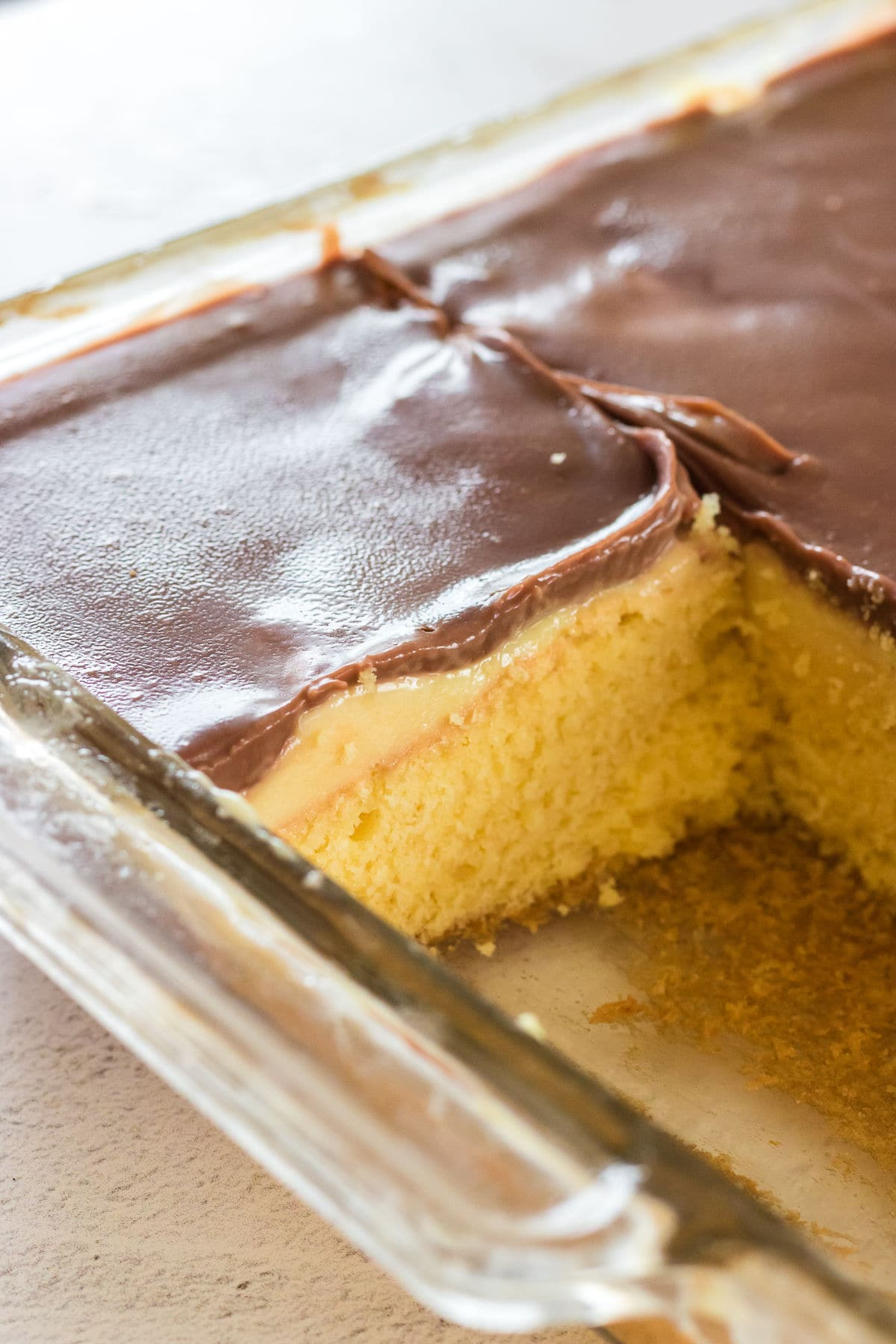 Close up of the cake in the baking pan with one serving removed.