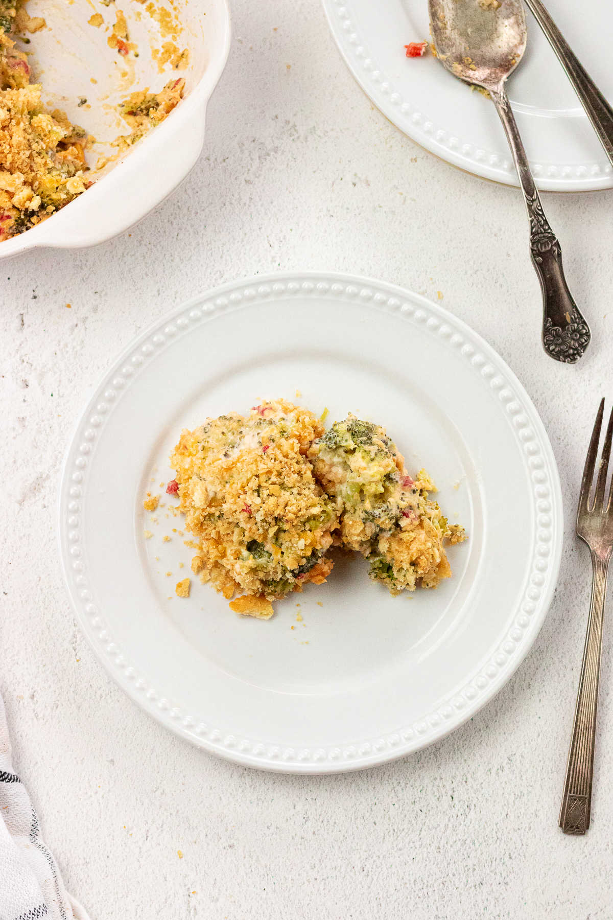 Overhead shot of a serving of broccoli cheese casserole on a white plate.