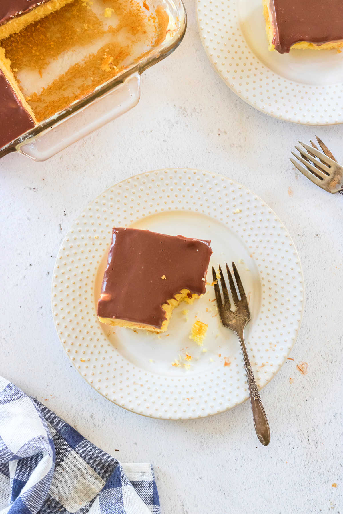 Overhead view of Boston cream pie poke cake on a plate with a fork nearby.