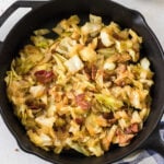 Closeup of fried cabbage and bacon in a skillet.