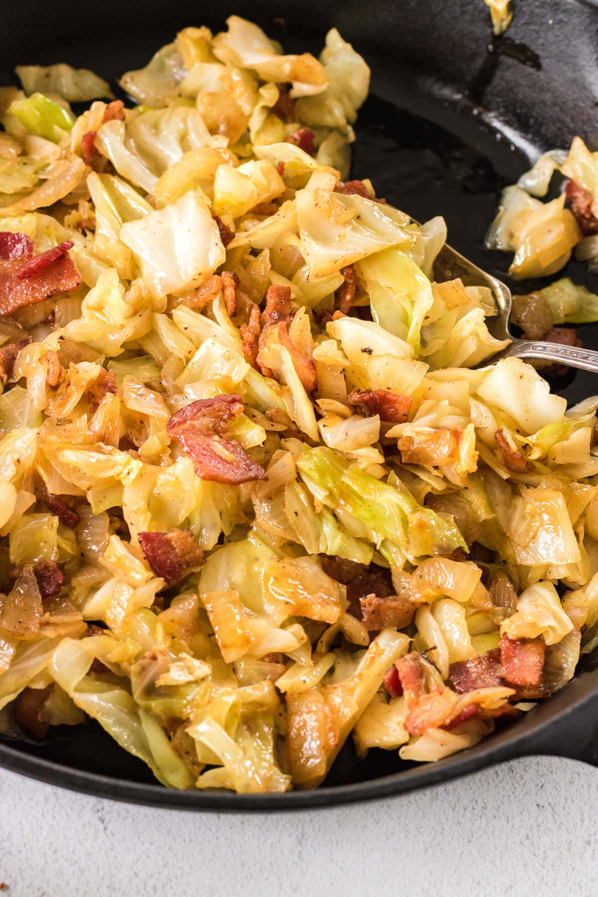 Closeup of this fried cabbage recipe showing the crispy bacon and tender vegetables.