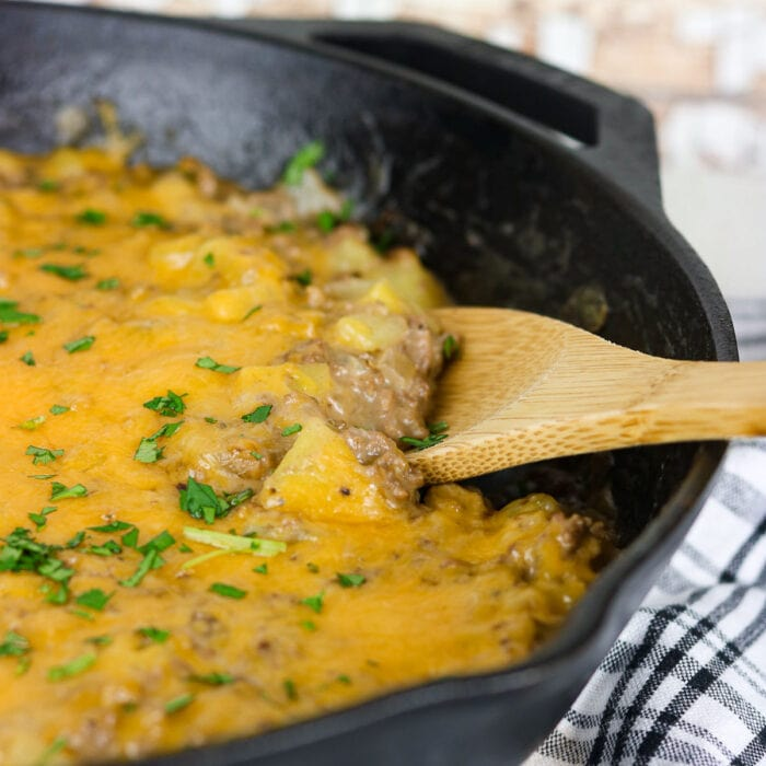 A wooden spoon serving a cheesy casserole from a skillet.