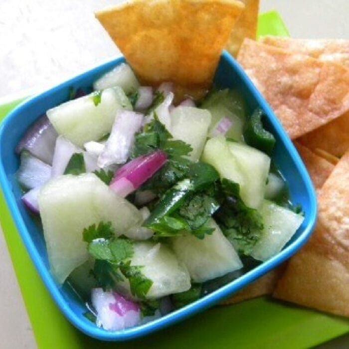 Chips and a refreshing honey dew salsa dip on a table.