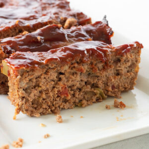 Close up of sliced meatloaf with glaze on top for feature image.
