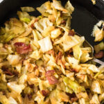 Close up of cabbage and bacon in a skillet with a text overlay for Pinterest.
