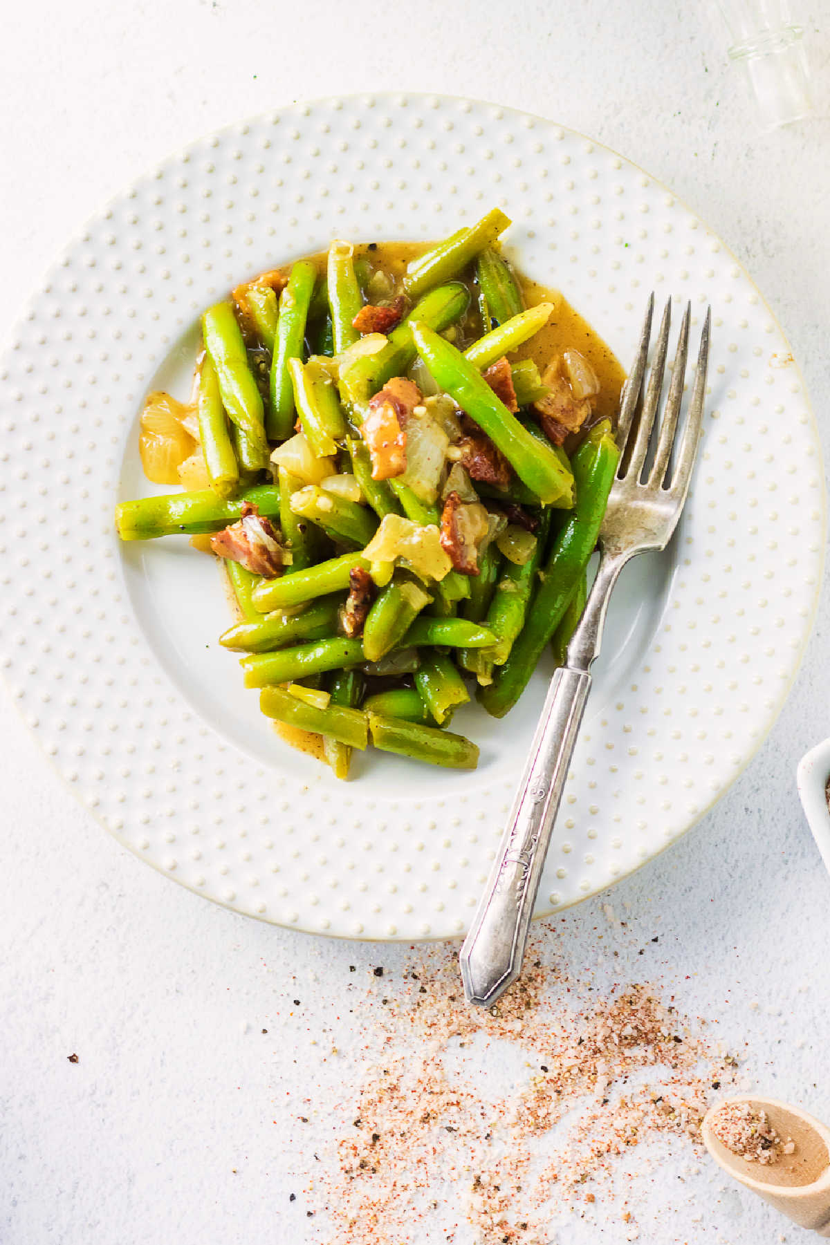 Overhead view of southern green beans on a white plate.