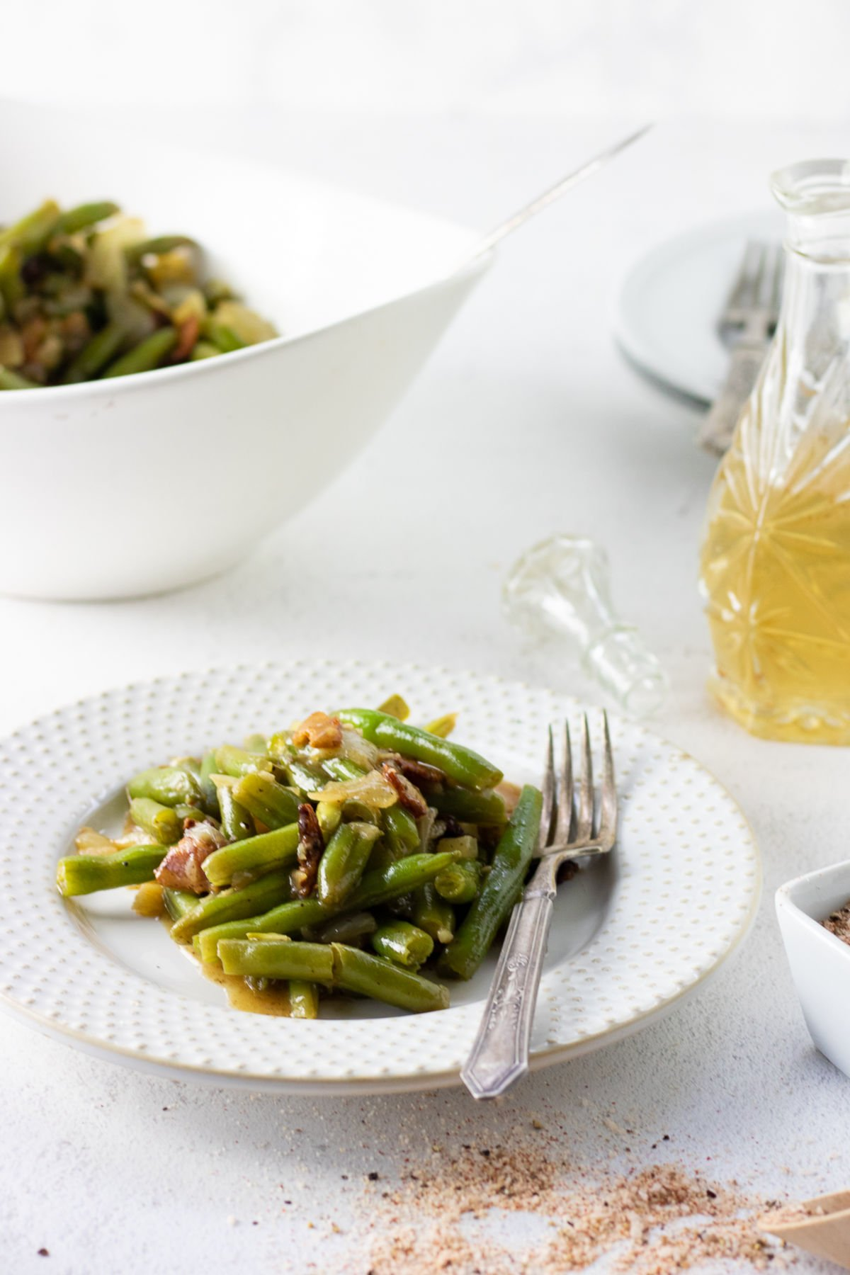 A plate of green beans on a table with the serving bowl in the background.