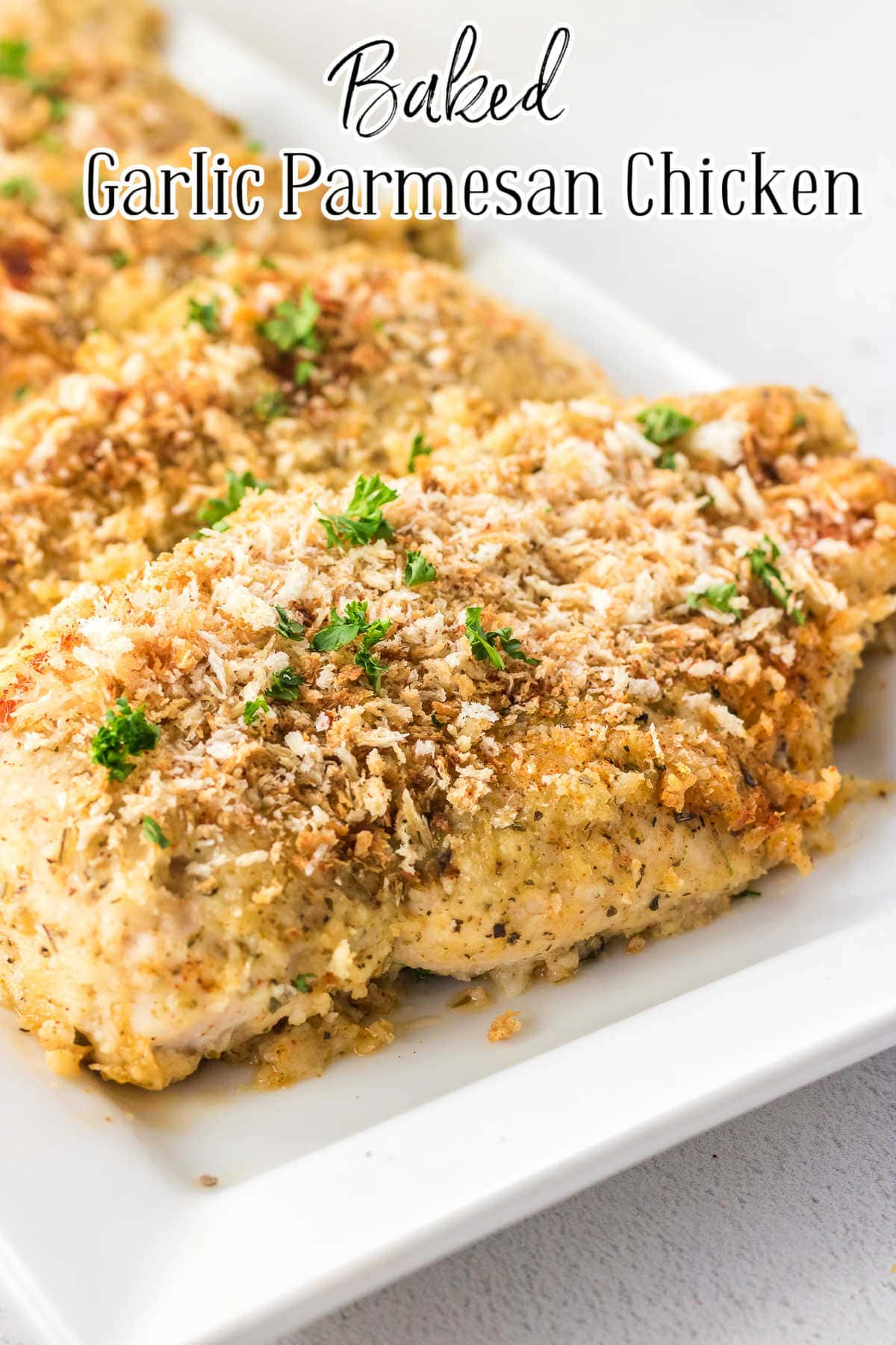 Closeup of breaded chicken breasts on a white plate.