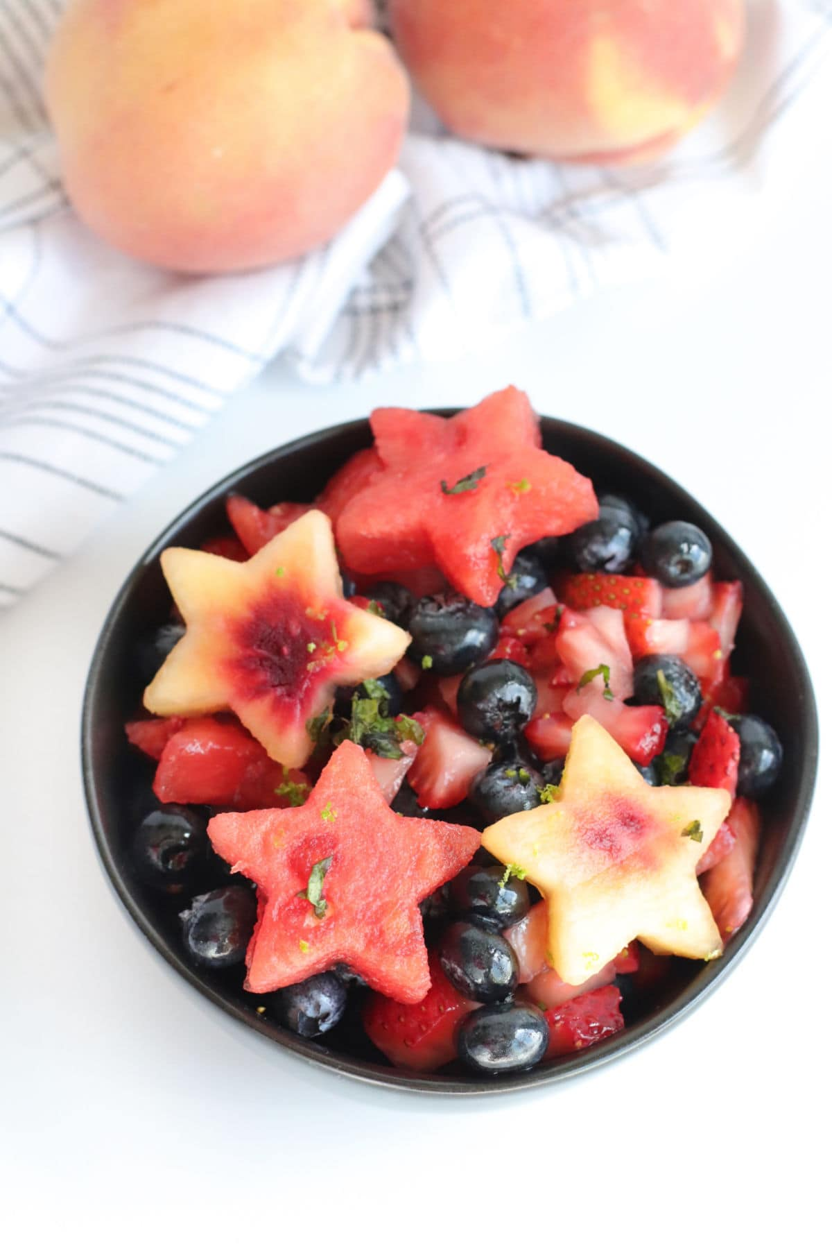 Overhead view of a bowl with watermelon and peach slices cut like stars and fresh blueberries.
