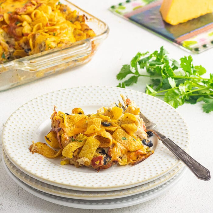 A serving of the finished Frito casserole on a plate with the casserole pan in the background.