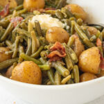 Side view of a serving dish of green beans and potatoes with a text overlay for Pinterest.