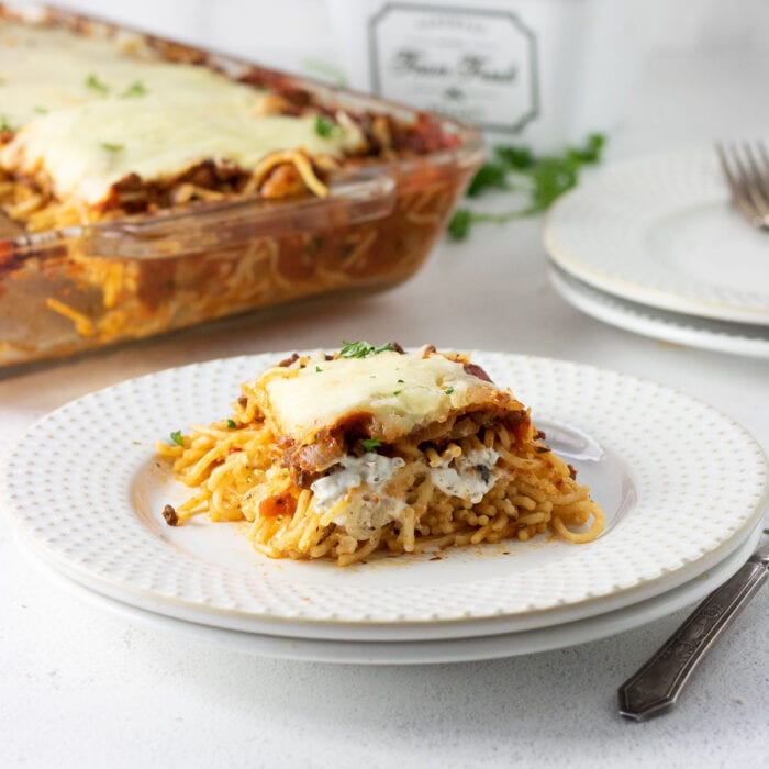 A serving of spaghetti casserole on a white plate with the casserole dish in the background.
