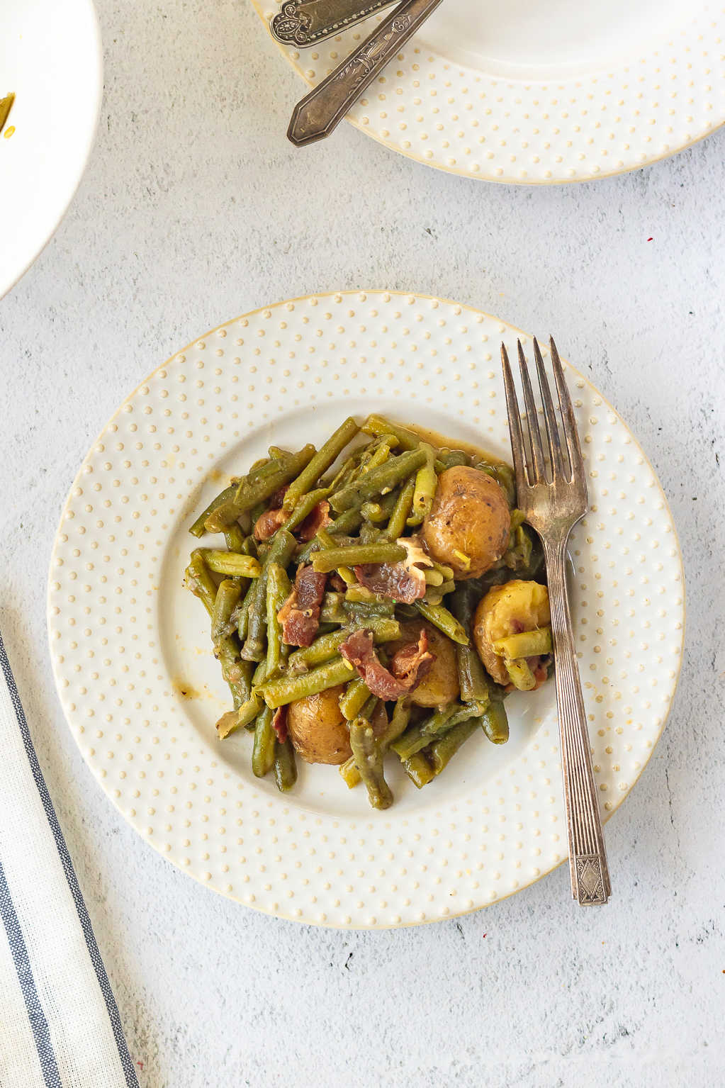 An overhead view of a serving of green beans and potatoes on a white plate.
