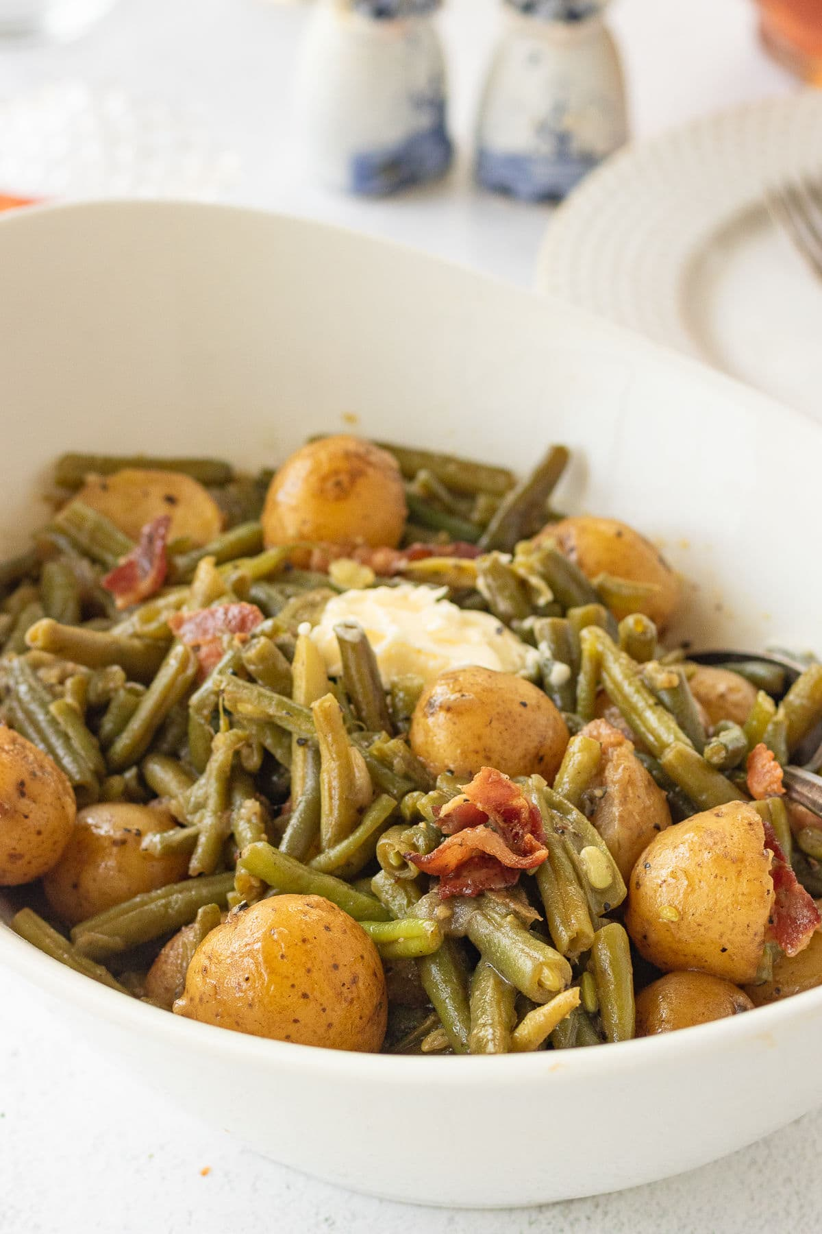 Closeup of a serving dish with cooked green beans and tender new potatoes in it.