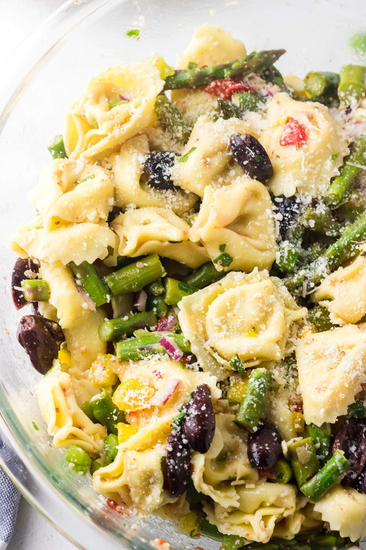 Close up of a bowl of tortellini and asparagus salad.