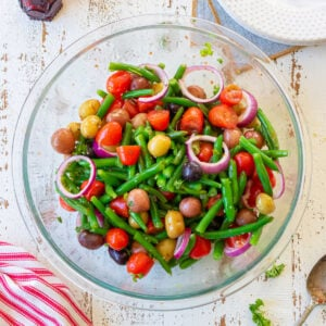 Overhead view of a bowl of green beans, tomatoes, potatoes, and red onions created for the feature image of this post.
