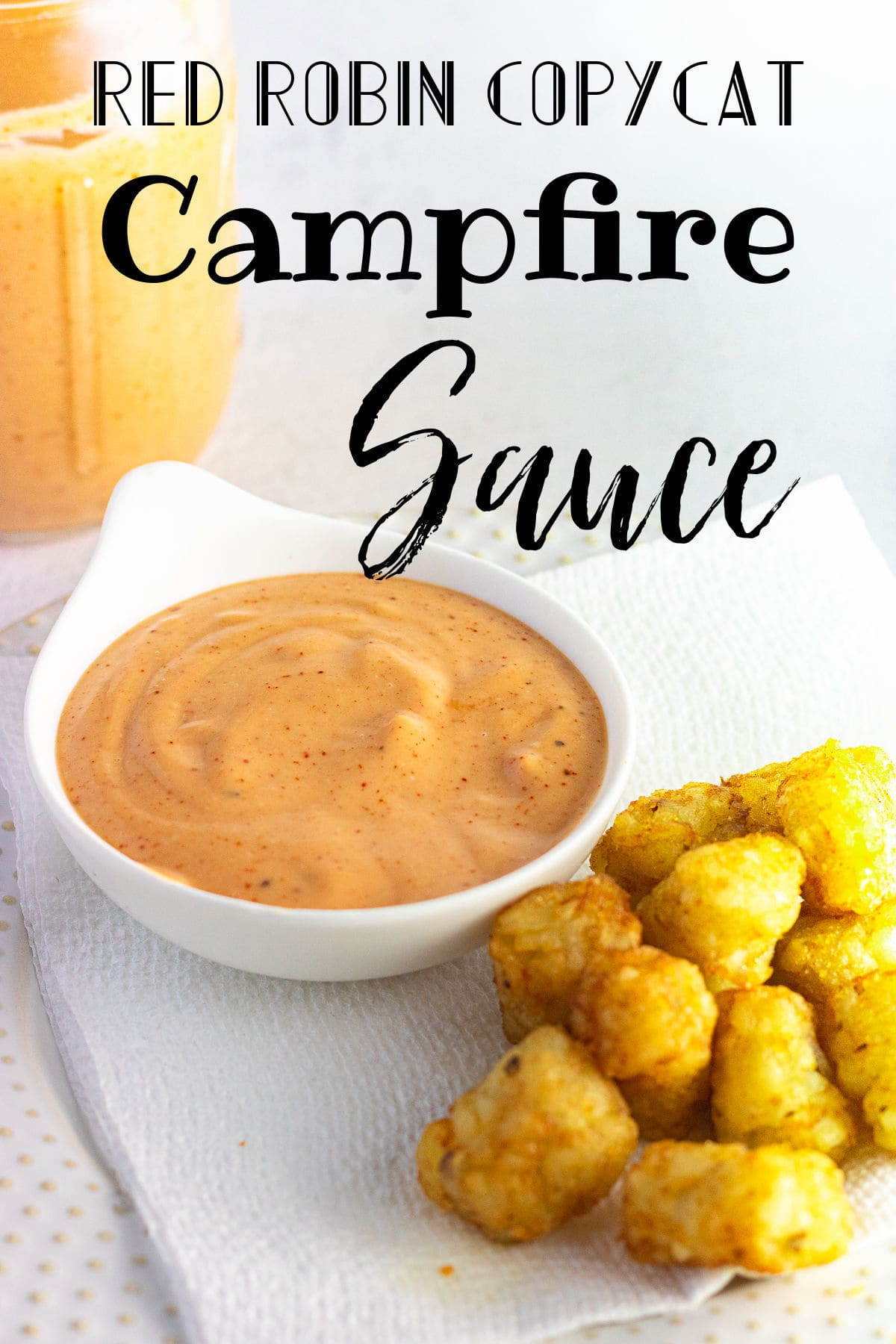 The orange dipping sauce in a bowl on a table.