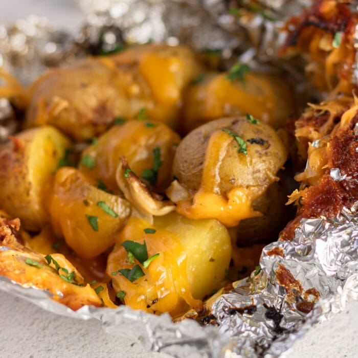 Closeup of finished potatoes covered in melted cheese.