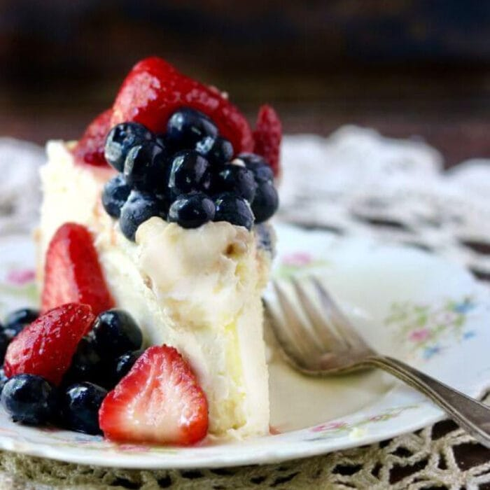 Slice of cheesecake with strawberries and blueberries on top.