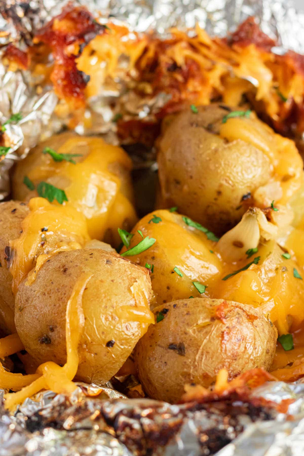 Open foil packet with cooked Yukon Gold potatoes inside.
