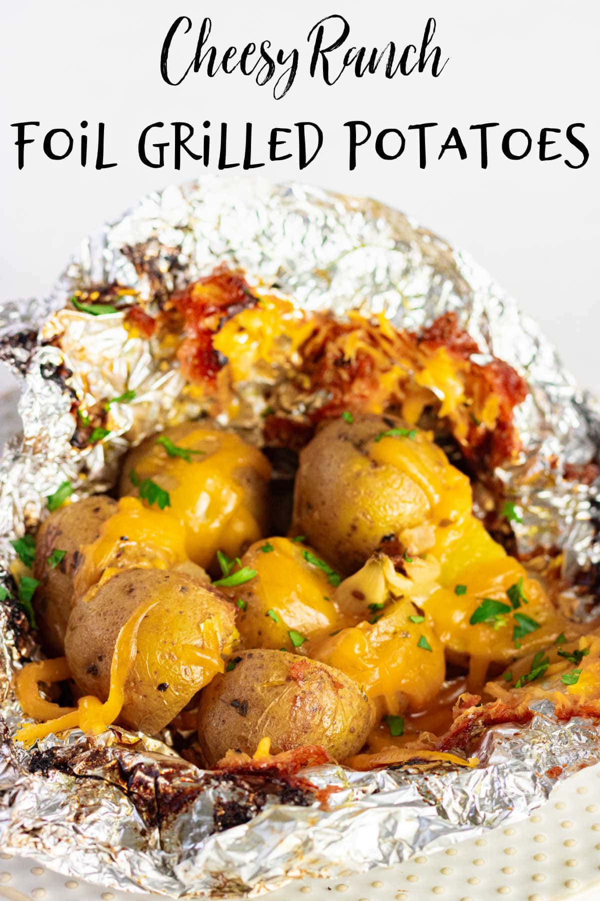 A closeup of cooked potatoes with cheese in an open foil packet.