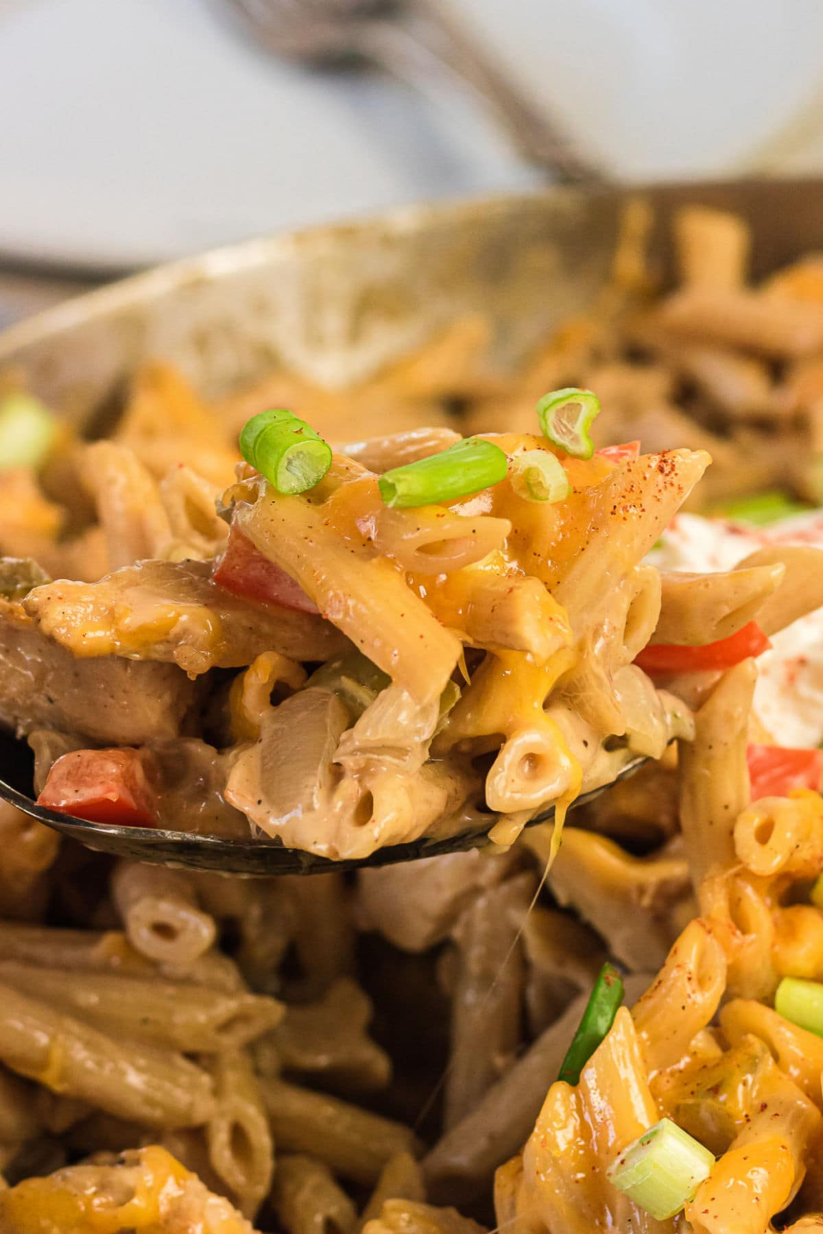 Closeup of a serving of chicken fajita pasta being removed from a pan.