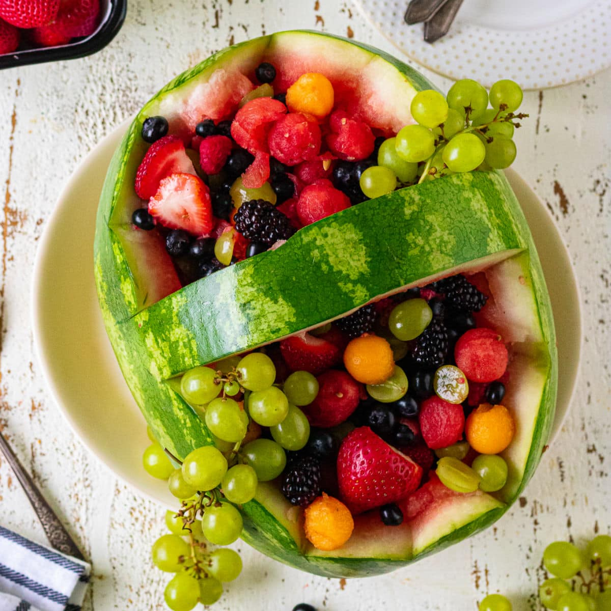 Overhead view of the finished watermelon basket filled with an assortment of fruit.