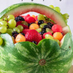 A finished watermelon basket with a text overlay for Pinterest.