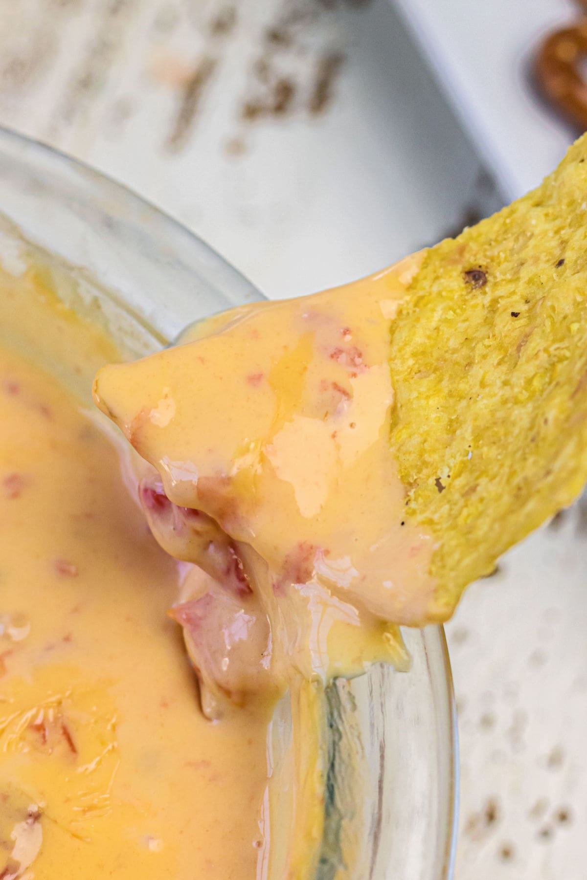 A tortilla chip being dipped into the queso.