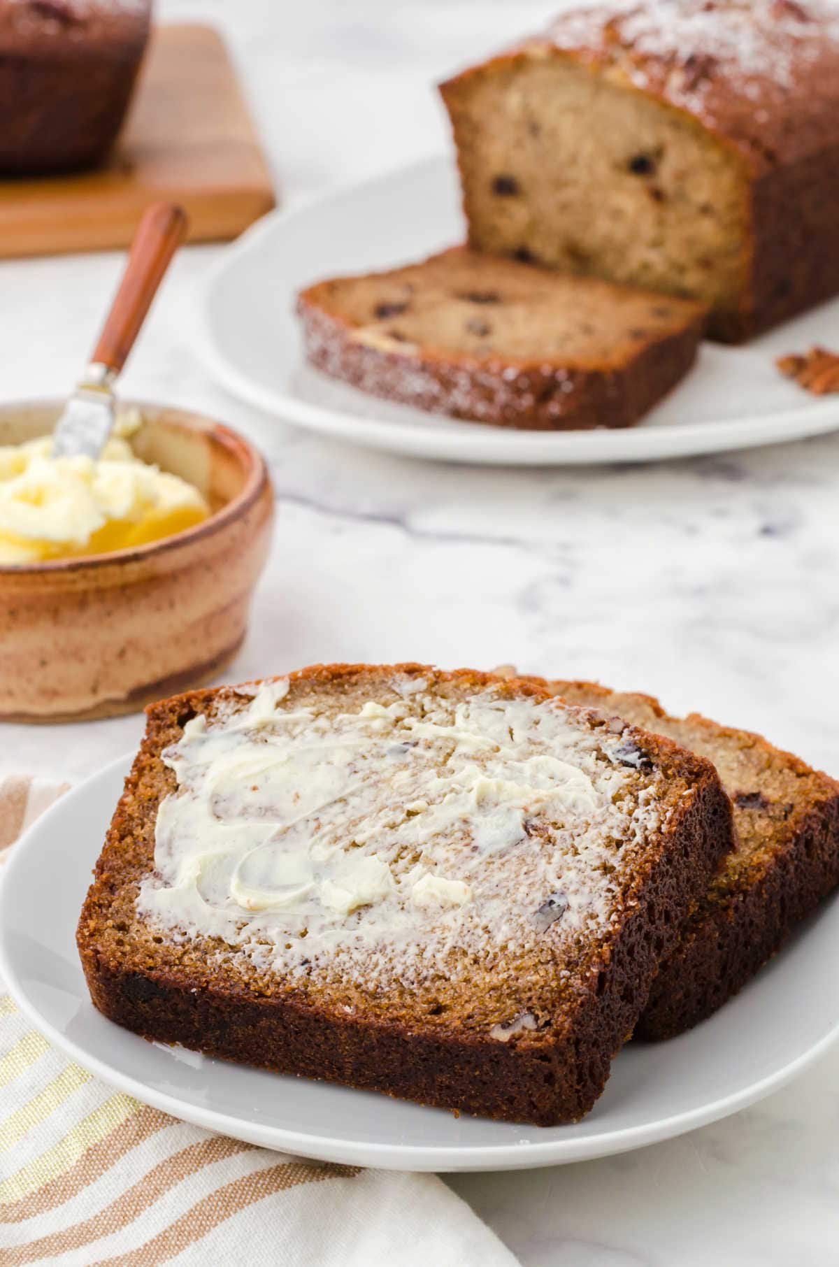 Slices of banana bread on a plate with butter spread over them.