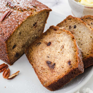 Slice of buttermilk banana bread showing the pecans and chocolate chips.