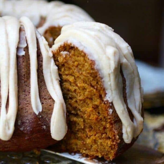 A slice of pumpkin spice bundt cake with white glaze being served.