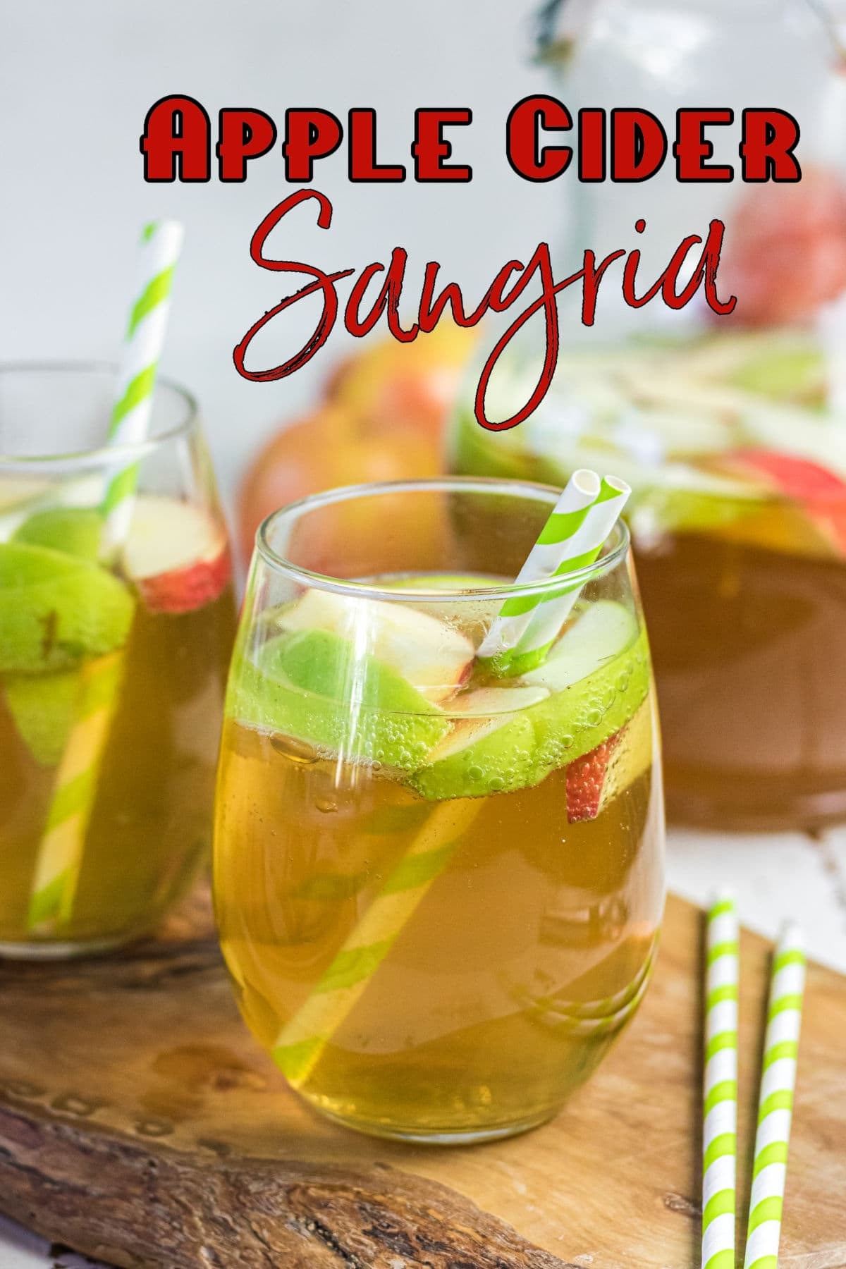 Close up of a glass of the sangria with apples floating in it. Title text overlay.