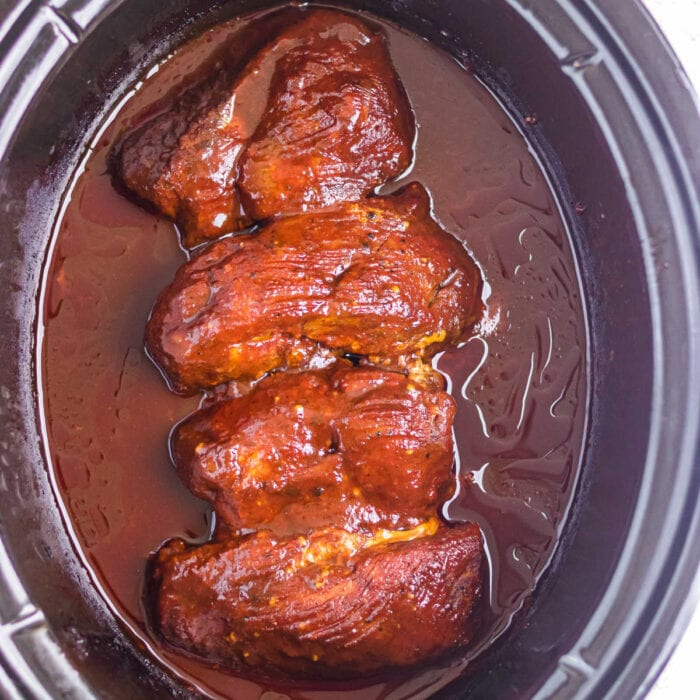 Overhead view of the finished meat in a slow cooker.