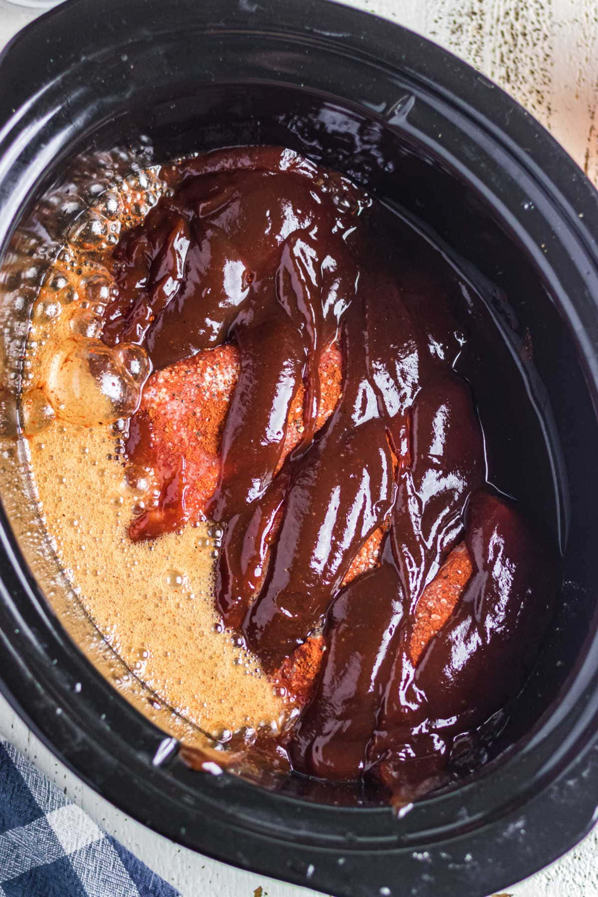 Image shows the remaining ingredients being added to the slow cooker.