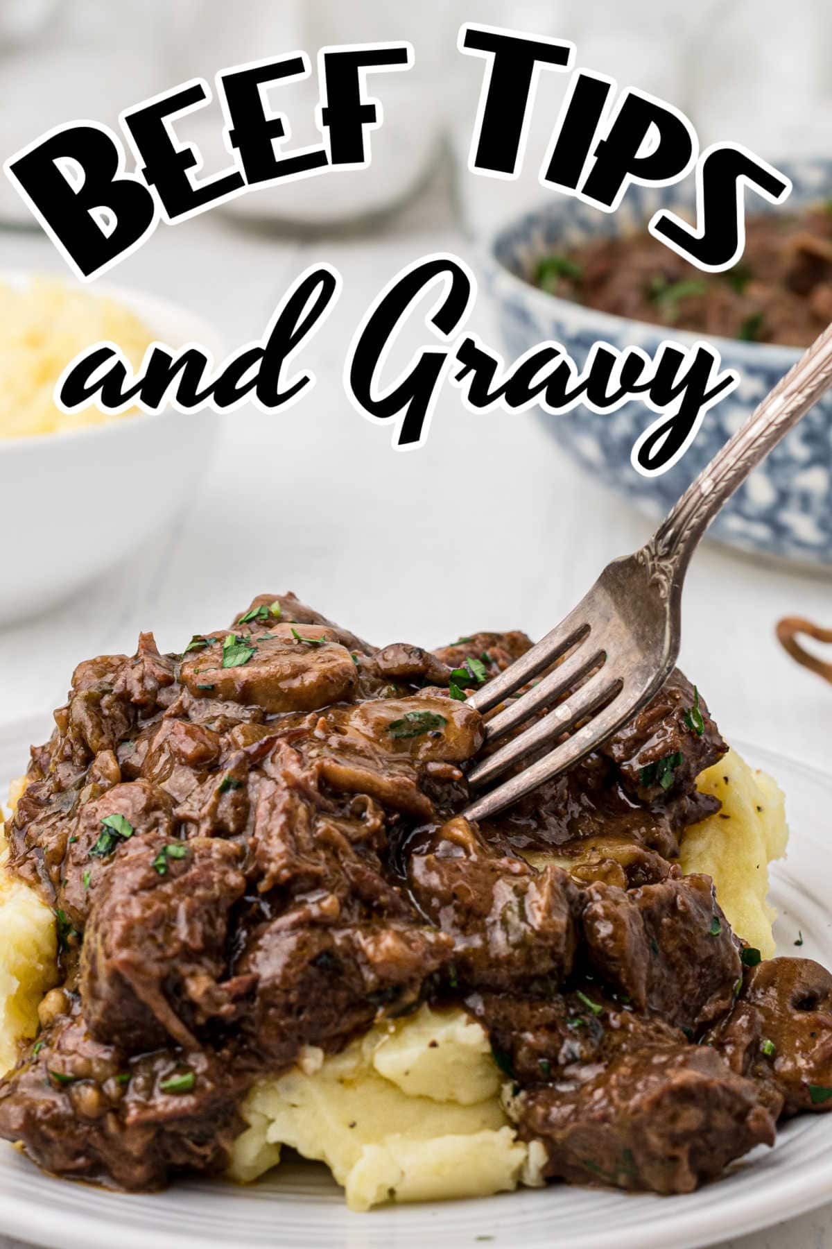 A fork in a serving of luscious beef and mashed potatoes. Title image for beef tips and gravy.
