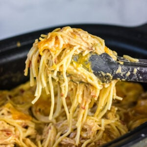 Tongs holding serving of pasta over slow cooker.
