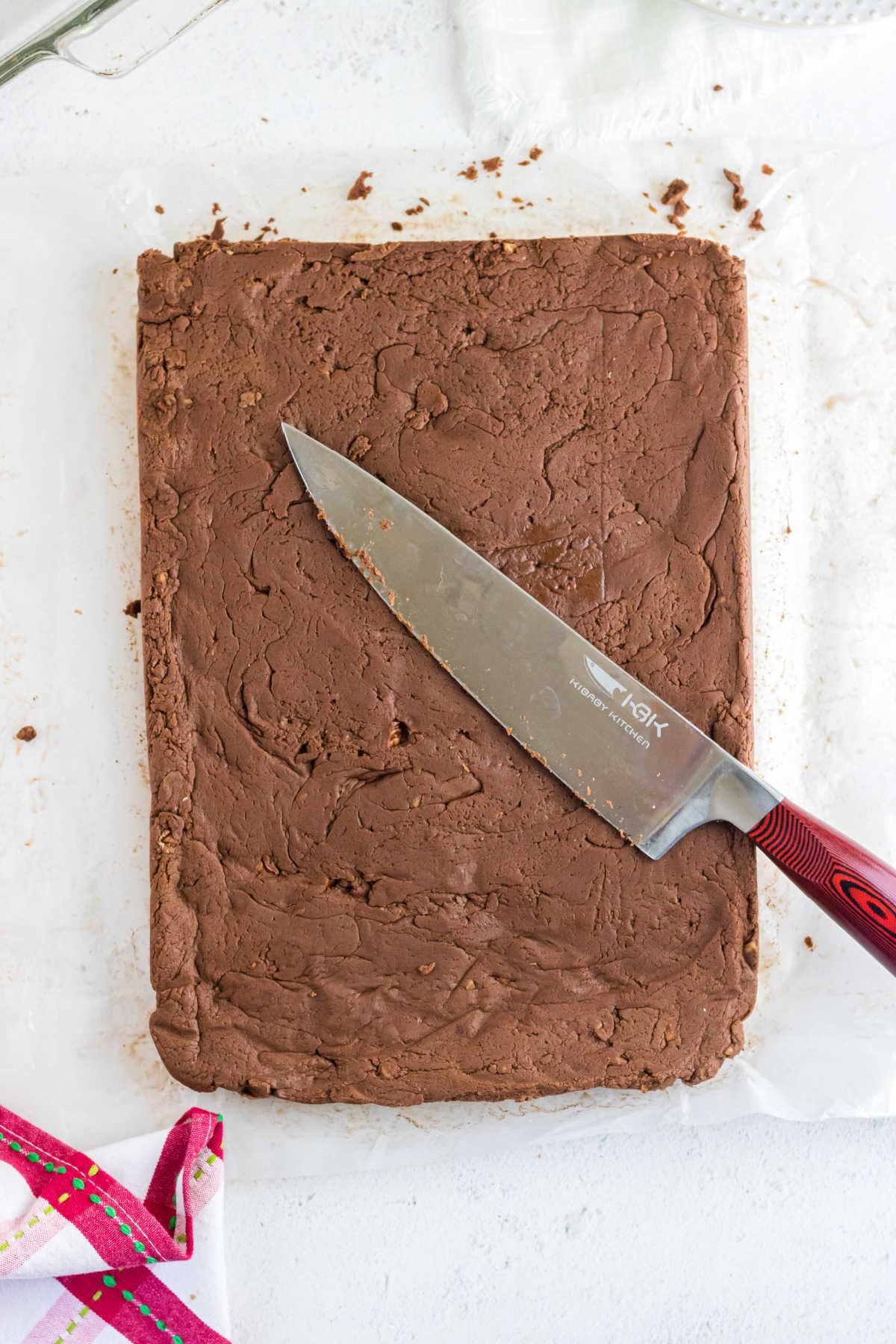 Overhead view of a slab of uncut fudge with a sharp knife on top.